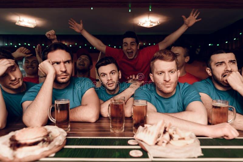 哀伤的蓝色队扇动在酒吧在有庆祝和欢呼在背景中的红色队爱好者的娱乐酒吧 免版税库存照片
