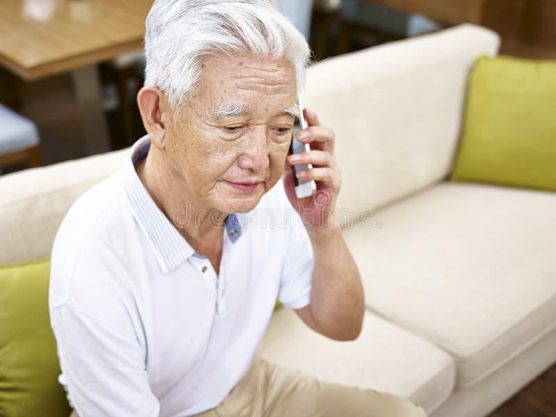 哀伤的资深亚裔人谈话在手机 图库摄影