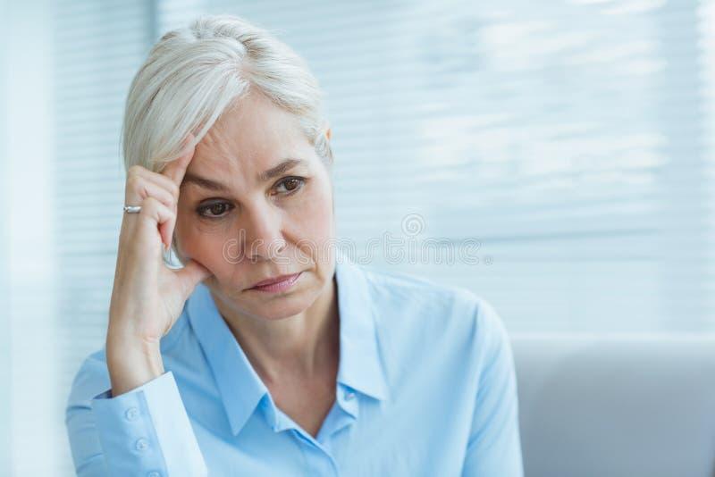 哀伤的资深妇女在家 免版税库存照片