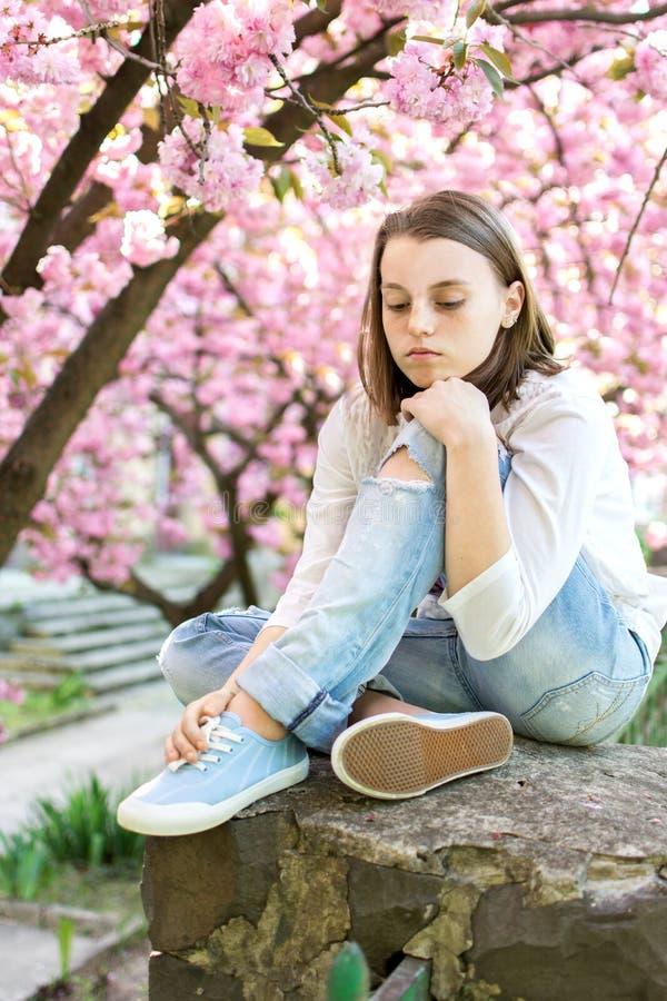 哀伤的青少年的女孩坐开花的樱桃树背景  免版税库存图片