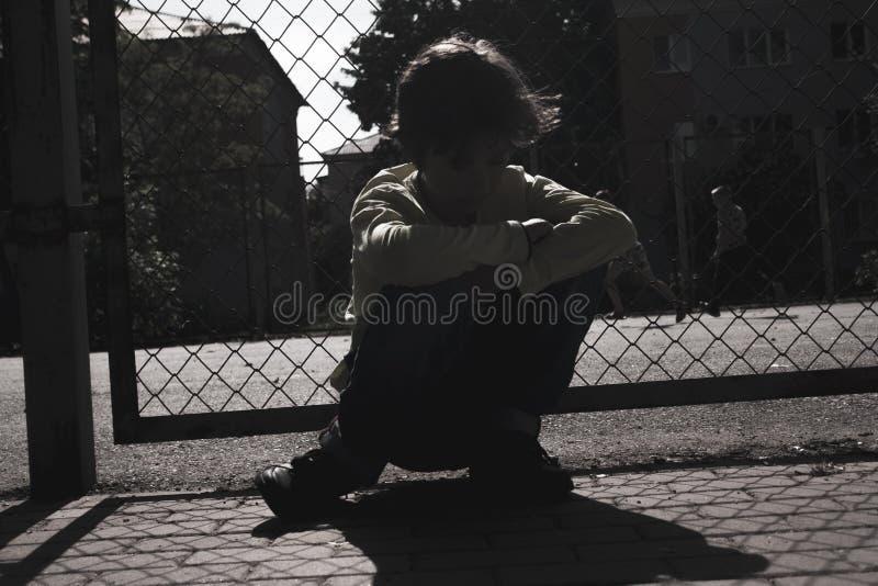 哀伤的青少年的男孩室外操场剪影  o 免版税库存照片