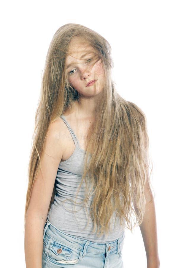 年轻哀伤的青少年的女孩在白肤金发的波浪发后掩藏反对白色b 库存图片