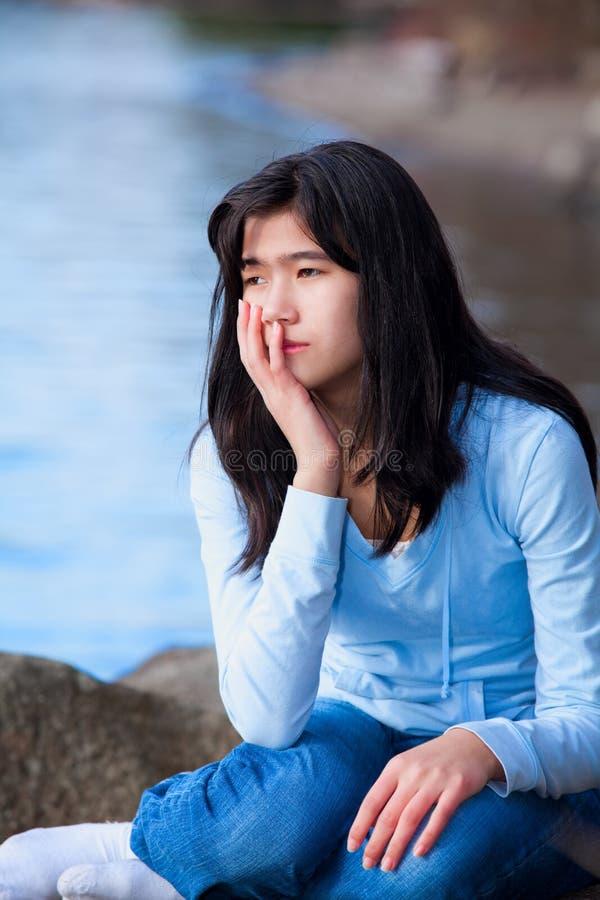 哀伤的青少年的女孩坐沿湖岸,偏僻的表示的岩石 免版税库存照片