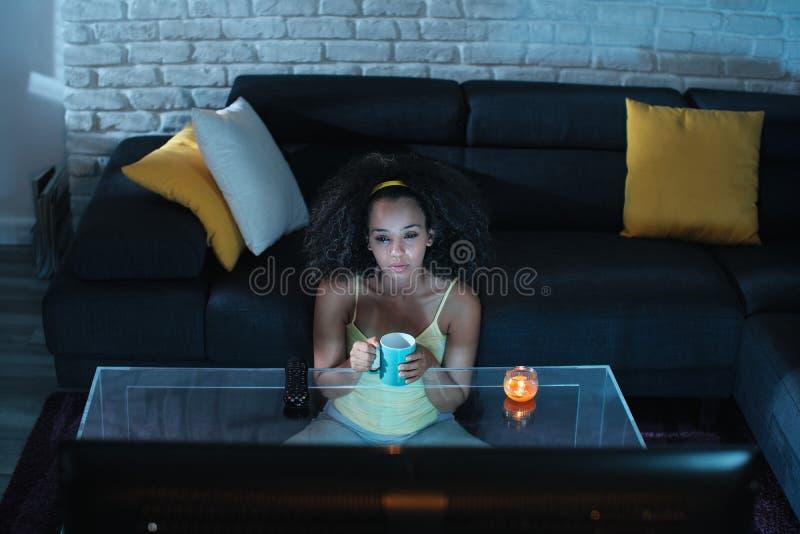 哀伤的黑人妇女观看的戏曲电视节目和哭泣 库存图片
