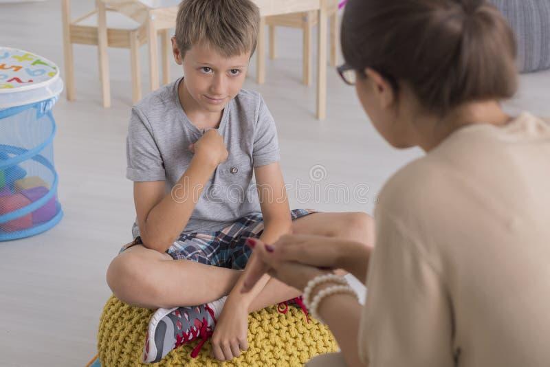 哀伤的年轻男孩坐蒲团 图库摄影