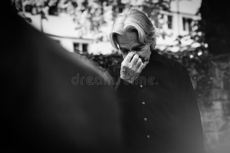 哀悼由一个心爱的` s坟墓的老人 免版税库存图片