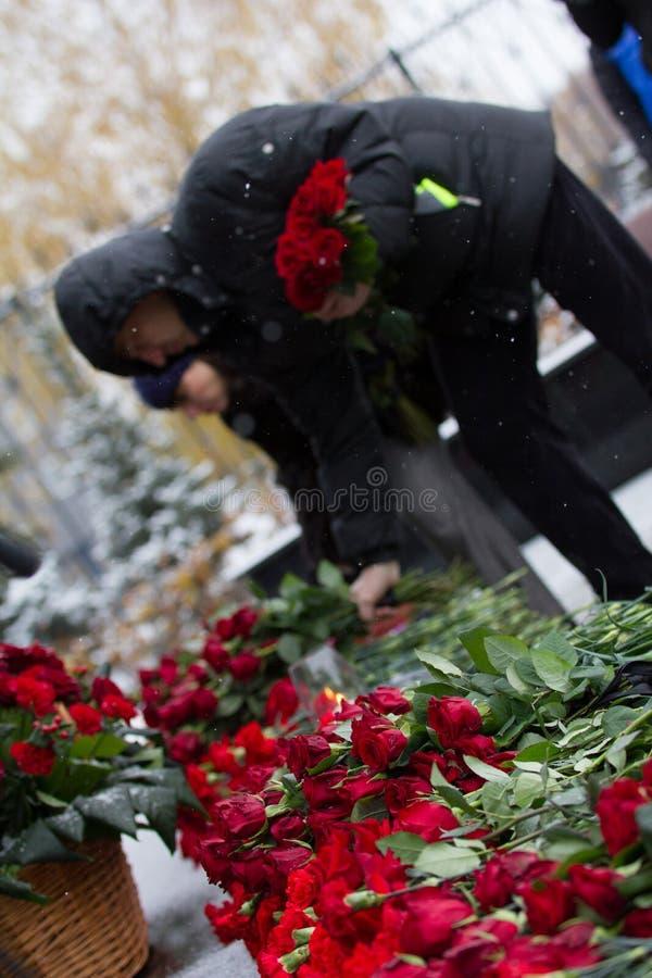 哀悼的康乃馨标志-放置开花对纪念碑 免版税库存图片