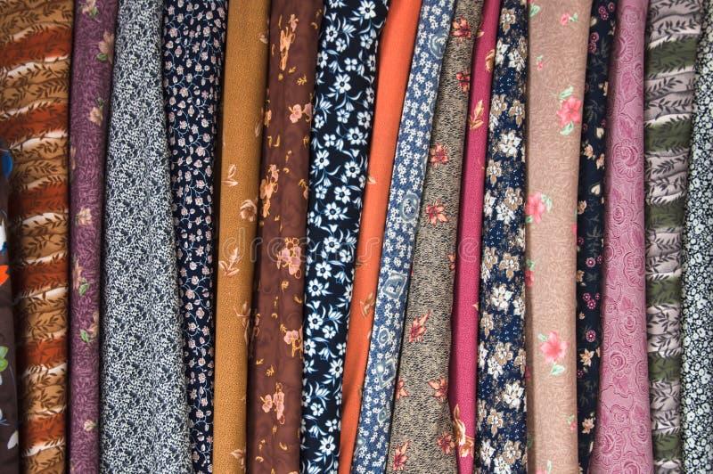 织品品种在挂衣架的在街市上。 免版税图库摄影