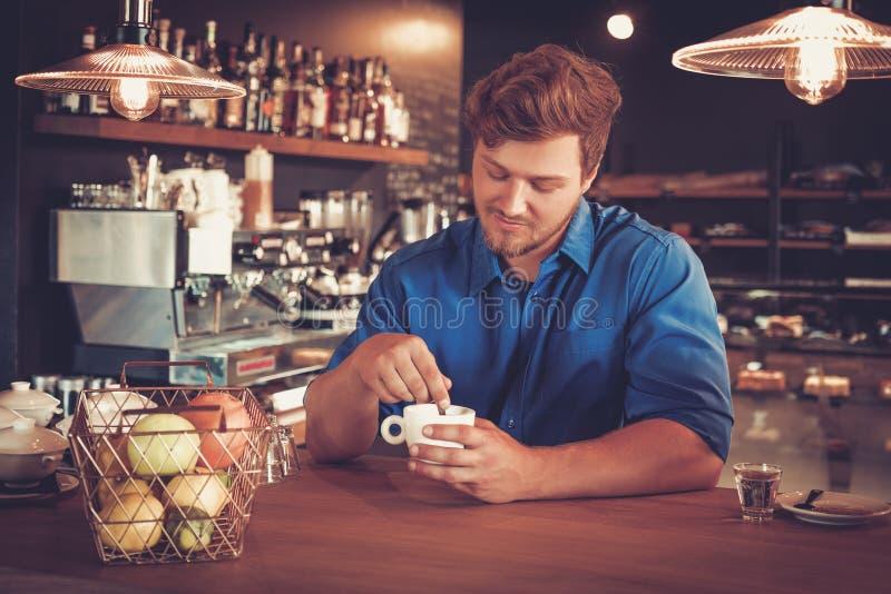 品尝咖啡的一个新型在他的咖啡店的Barista 库存图片