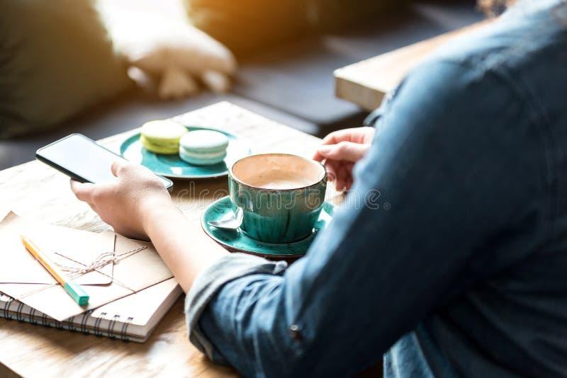 品尝咖啡的妇女在桌上 库存图片