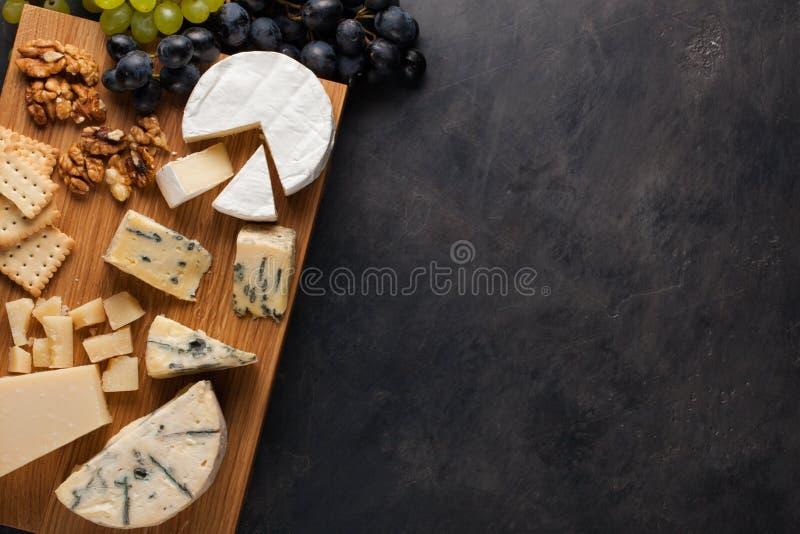 品尝在一块木板材的乳酪盘 酒的食物和浪漫,在一张黑暗的石桌上的乳酪熟食 与拷贝s的顶视图 免版税库存照片