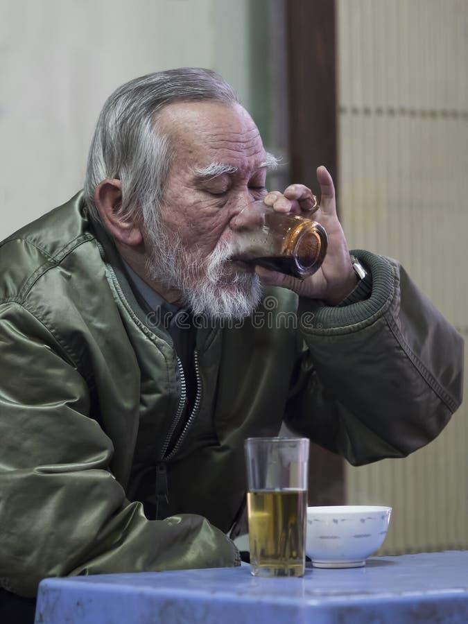 品尝强和黑暗的越南的强烈的乐趣的老人 免版税库存图片