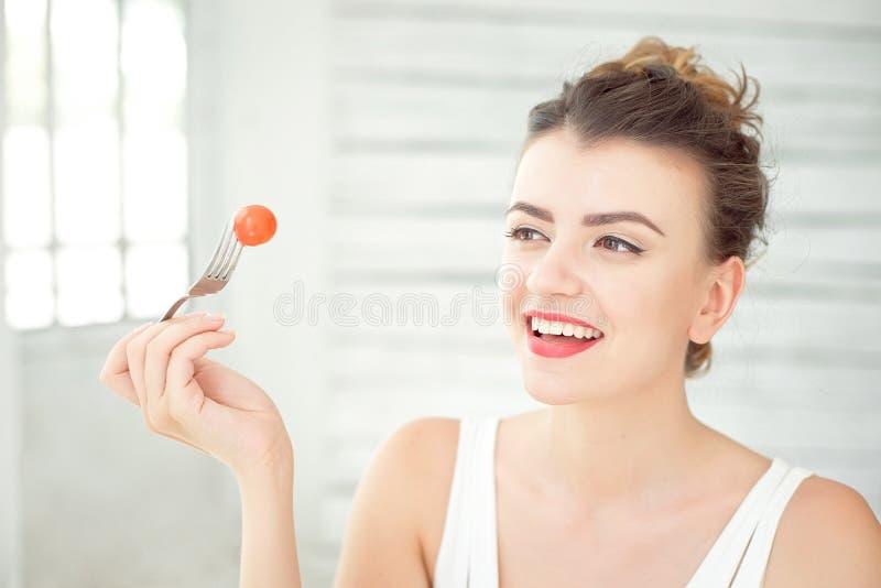 品尝新鲜的有机西红柿的年轻微笑的妇女在一间白色明亮的屋子坐 概念健康生活方式 免版税库存照片
