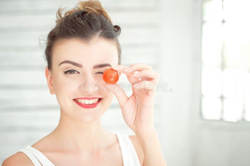 品尝新鲜的有机西红柿的年轻微笑的妇女在一间白色明亮的屋子坐 概念健康生活方式 库存照片