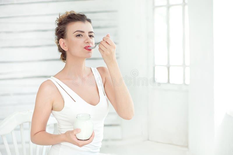品尝新鲜的有机酸奶的年轻微笑的妇女坐在白色明亮的室,佩带在白色汗衫 健康 库存照片