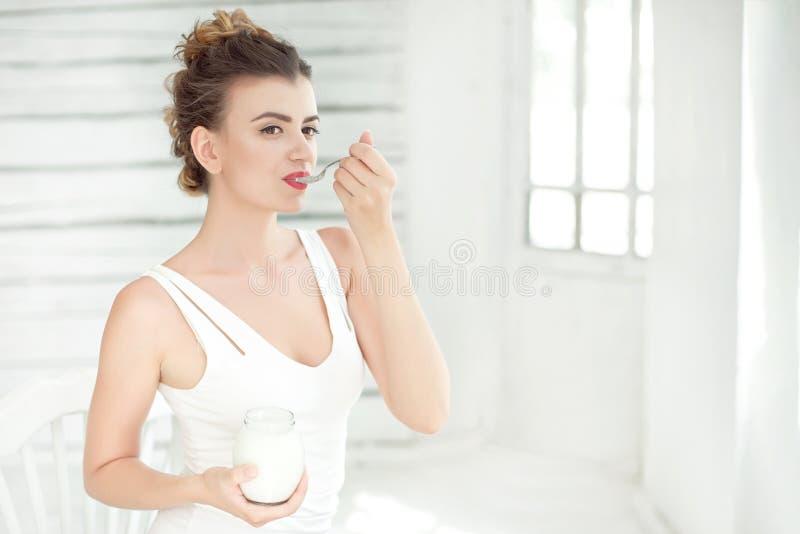 品尝新鲜的有机酸奶的年轻微笑的妇女坐在白色明亮的室,佩带在白色汗衫 健康 免版税库存照片