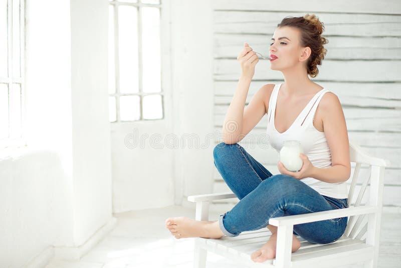 品尝新鲜的有机酸奶的年轻微笑的妇女坐在白色明亮的室,佩带在白色汗衫 健康 图库摄影