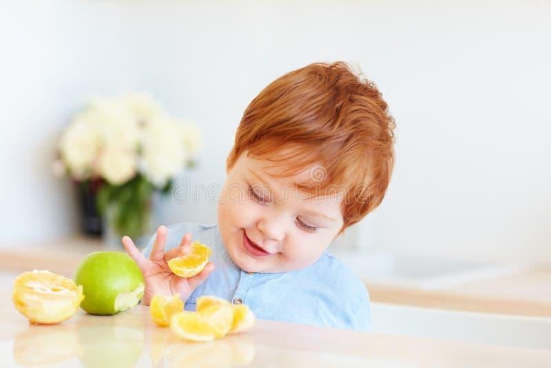 品尝橙色切片和苹果的逗人喜爱的红头发人小孩婴孩在厨房 免版税库存照片