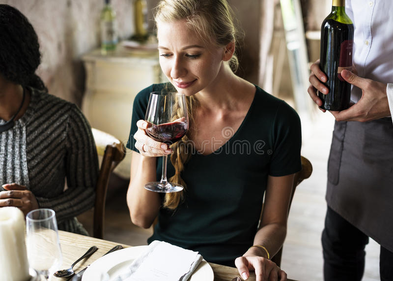 品尝红葡萄酒的妇女在一家优等的餐馆 图库摄影