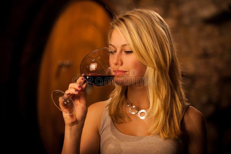 品尝红葡萄酒的美丽的年轻白肤金发的妇女在葡萄酒库里
