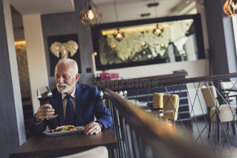品尝酒的资深商人在餐馆 图库摄影
