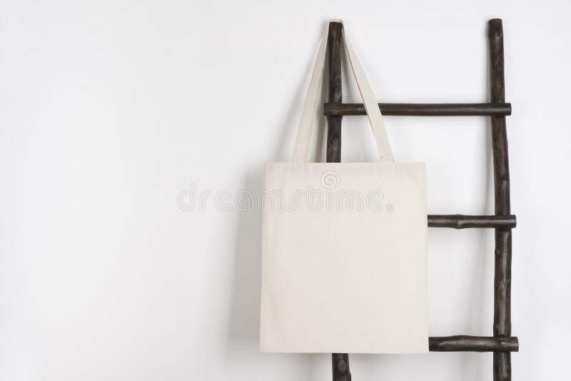 织品布料垂悬在葡萄酒木活梯的购物袋大模型 图库摄影