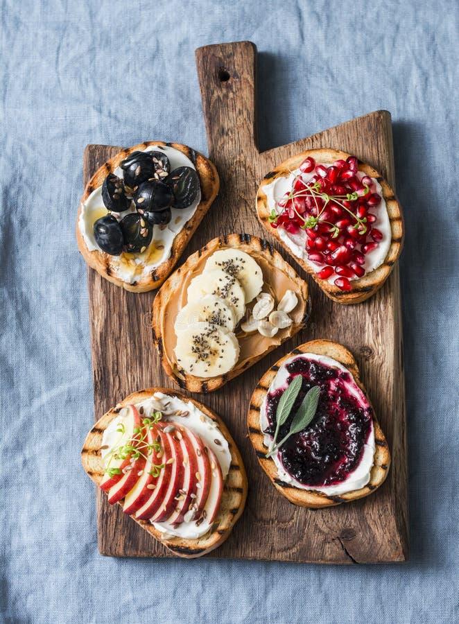 品种烤面包点心三明治用乳脂干酪和苹果,石榴,果酱,葡萄,花生酱,香蕉,亚麻籽, 库存图片