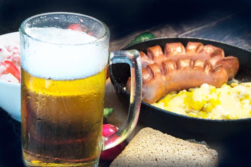 品脱在一块misted玻璃的泡沫的啤酒,在一顿可口晚餐的背景 免版税库存照片