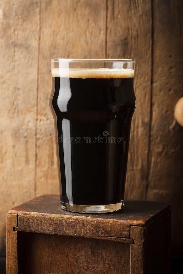 品脱在桶附近的烈性黑啤酒 图库摄影