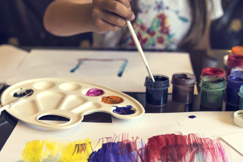 哄骗与刷子和树胶水彩画颜料墨水的女孩绘画在白皮书,愉快和乐趣五颜六色的青年图画,童年概念 图库摄影
