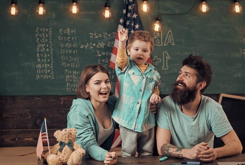 哄骗与父母在有美国旗子的,在背景的黑板教室 爱国教育概念 美国家庭坐 免版税库存图片