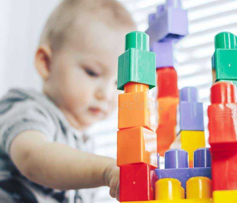 哄骗使用与从玩具建设者的块的男孩 未聚焦的婴孩,在玩具的焦点 免版税图库摄影