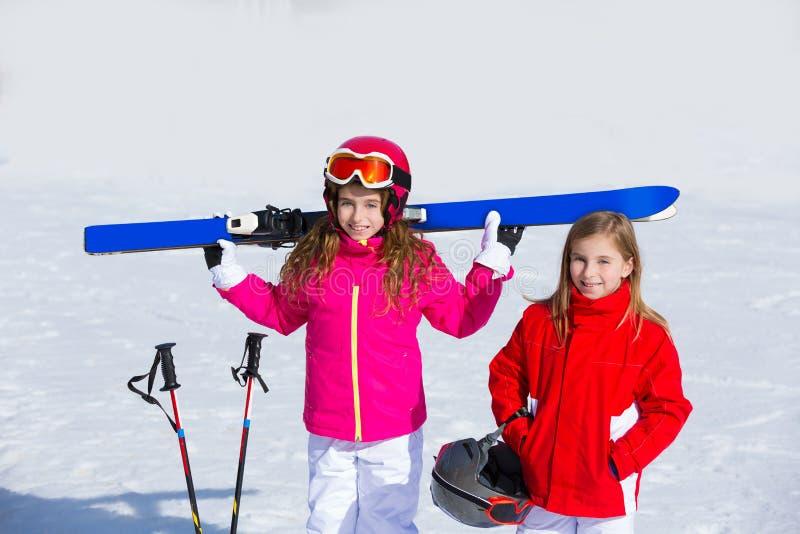哄骗冬天雪的女孩姐妹用滑雪设备 免版税库存照片