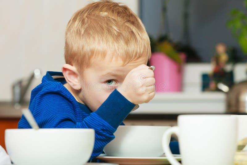 哄骗吃早餐、谷物和牛奶在碗的男孩 免版税库存图片