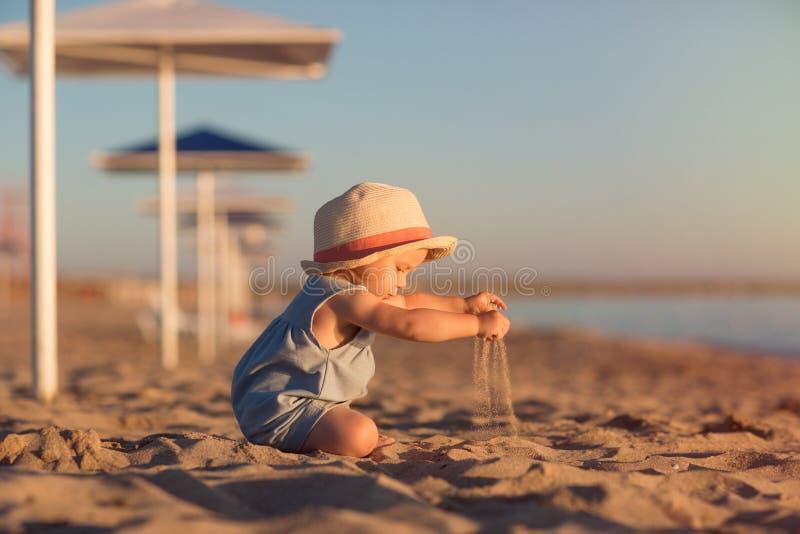 哄骗在使用与在海滩的沙子的帽子由海 与孩子的假日在海洋附近 免版税图库摄影
