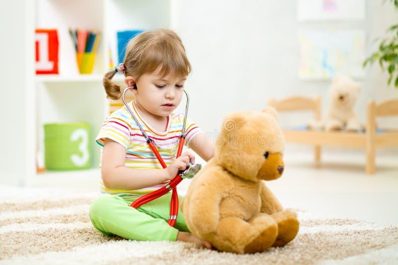哄骗在家扮演有长毛绒玩具的女孩医生 库存照片