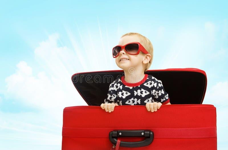 哄骗在手提箱,看旅行行李愉快的婴孩的孩子里面 图库摄影