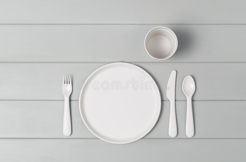 哄骗在灰色背景隔绝的淡色塑料碗筷 顶视图 库存照片