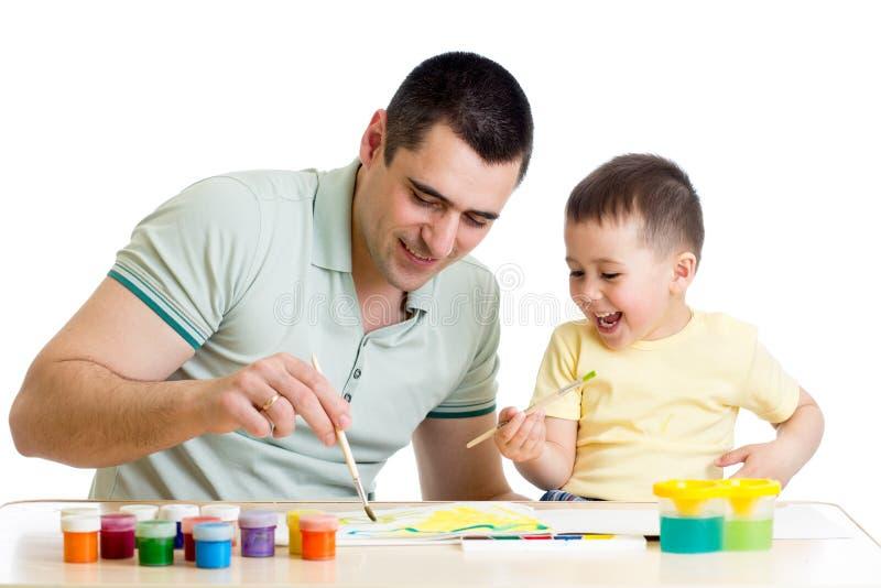 哄骗在白色一起隔绝的男孩和爸爸油漆 免版税图库摄影