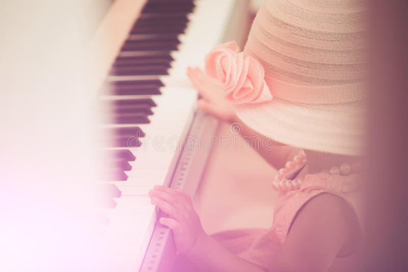 哄骗在葡萄酒桃红色帽子,礼服,小珠项链戏剧钢琴 库存照片