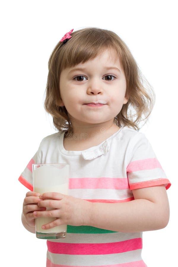 哄骗女孩饮用奶或酸奶从玻璃 免版税库存照片