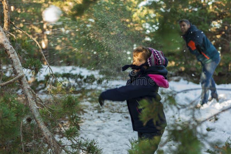 哄骗把在山坡的雪球扔出去 免版税库存图片