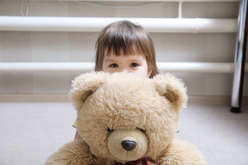 哄骗拥抱玩具熊室内在她的屋子里,热爱概念,在玩具后的孩子 免版税库存照片