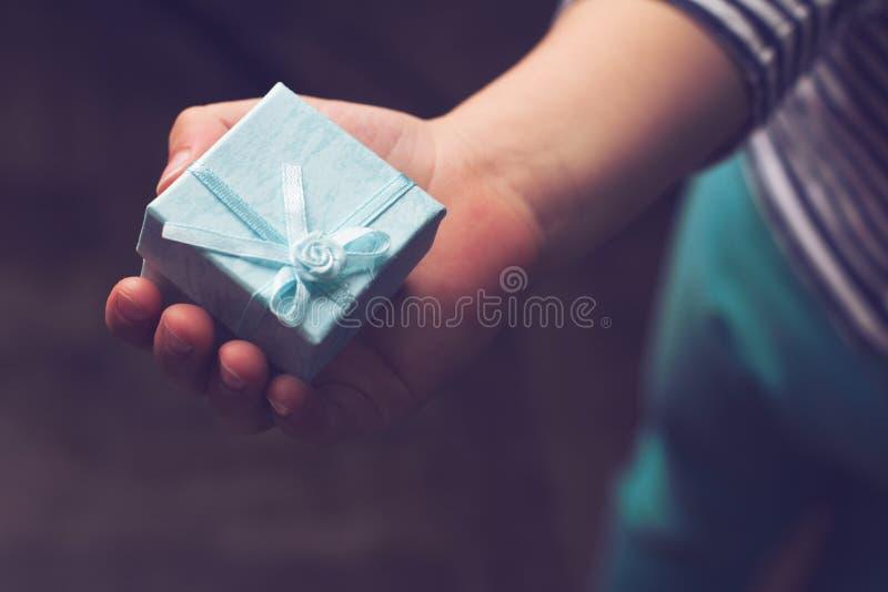 哄骗拿着有丝带的一个小蓝色礼物盒在他的手上 免版税图库摄影