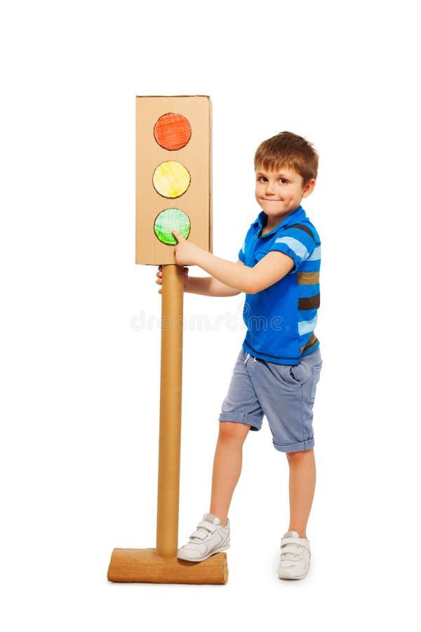 哄骗指向红绿灯绿色信号的男孩  免版税图库摄影