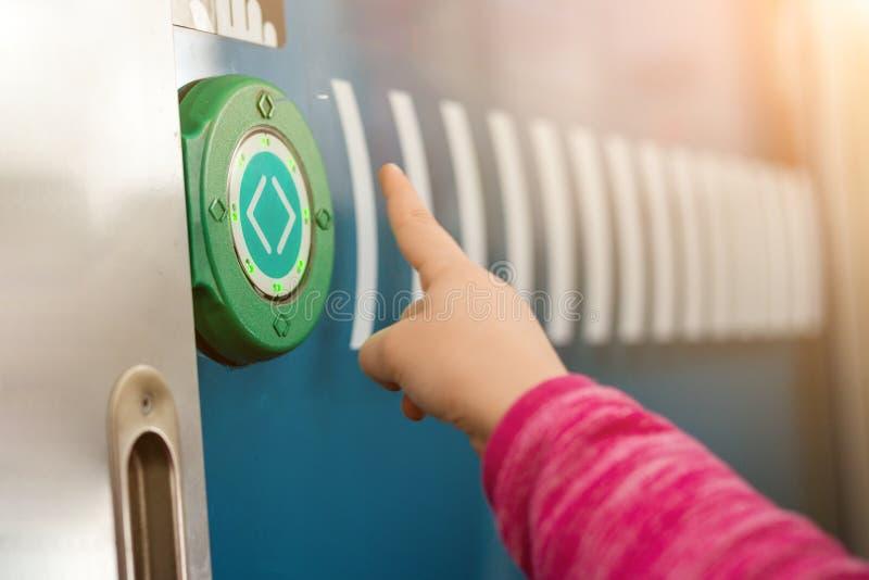 哄骗按有箭头的手指绿色圆的接触按钮 在支架之间的透明门在城市间的火车 技术现代的sensot 免版税库存照片