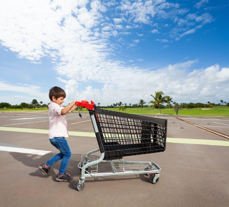 哄骗推挤空的购物车的男孩在停车场 免版税库存照片