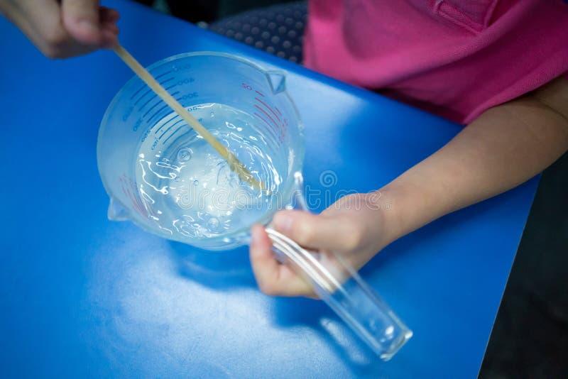 哄骗搅动在量杯的手白色粉末有木chopst的 图库摄影
