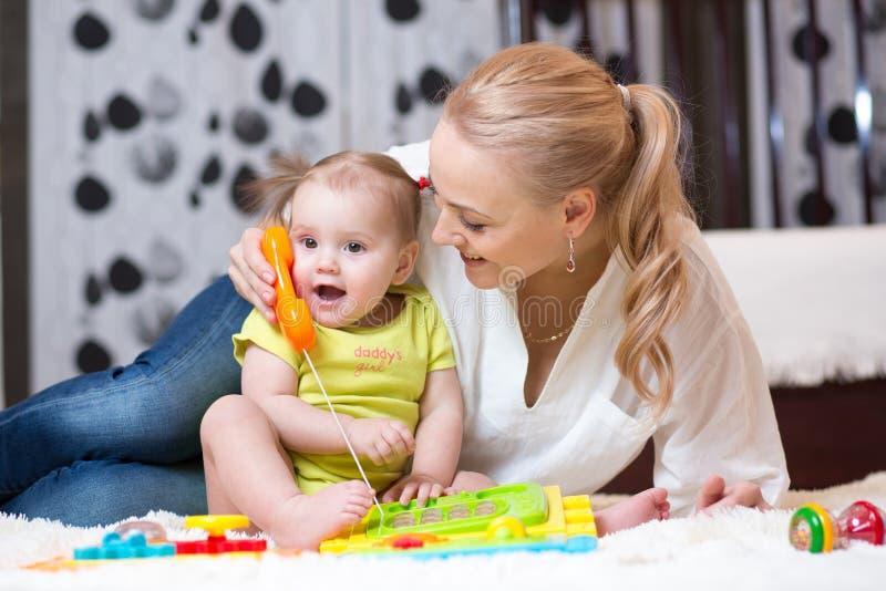哄骗有母亲的女孩电话-使用与玩具电话 库存照片