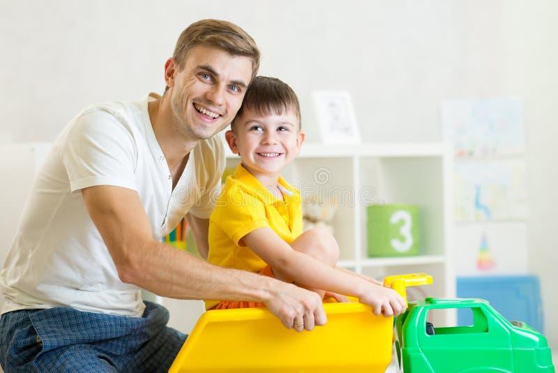 哄骗男孩和他的爸爸戏剧与玩具树干 库存图片